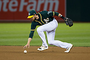 Oakland Athletics second baseman Jed Lowrie (8) scoops up a ground ball with his hand against the San Francisco Giants at Oakland Coliseum in Oakland, California, on August 1, 2017. (Stan Olszewski/Special to S.F. Examiner)