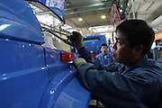 Production line workers assemble a 'Jie Fang' model truck at the China First Auto Works plant in Changchun, China May 25, 2004. China FAW Group Corp., which makes cars in the world's fastest-growing car market with Volkswagen AG, Toyota Motor Corp. and Mazda Motor Co., said its profit may be eroded by rising prices of steel and aluminum.