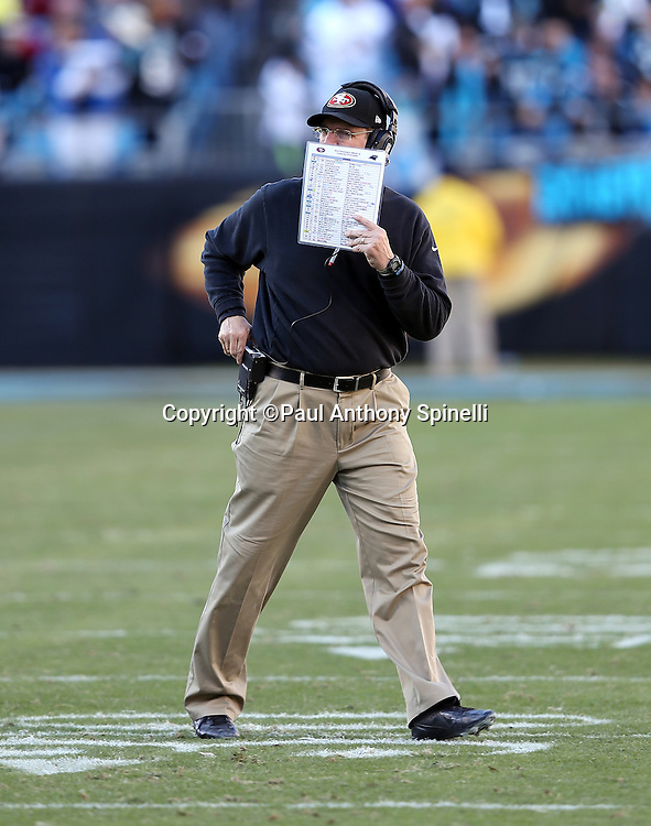 San Francisco 49ers head coach Jim Harbaugh walks on the field as he hides his mouth with his play chart during the NFC Divisional Playoff NFL football game against the Carolina Panthers on Sunday, Jan. 12, 2014 in Charlotte, N.C. The 49ers won the game 23-10. ©Paul Anthony Spinelli
