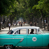 Cuba, Havana central, along el prado, blue car, people walking