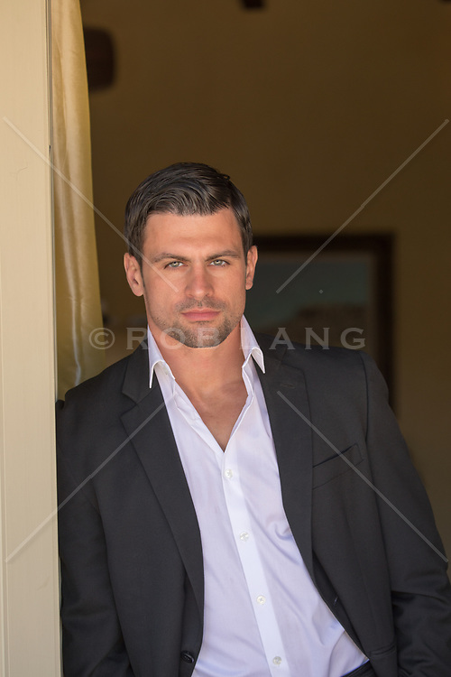handsome man with green eyes and dark hair in a jacket and button down shirt at home
