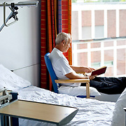 Nederland Rotterdam 25-08-2009 20090825 Foto: David Rozing ..Serie over zorgsector, Ikazia Ziekenhuis, man leest boek op ziekenzaal. Patient reading a book lto kill some time in hospitalroom. Holland, The Netherlands, dutch, Pays Bas, Europe, op zaal liggen..Foto: David Rozing