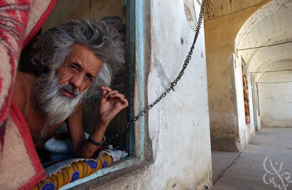 Ismatullah Saba, a mentally ill former professor, sits chained to a wall in his room at the Afghanistan Red Crescent Society May 16, 2002 in Kandahar. Workers at the facility say he has been chained up at the Society for approximately 32 years due to his mental illness.