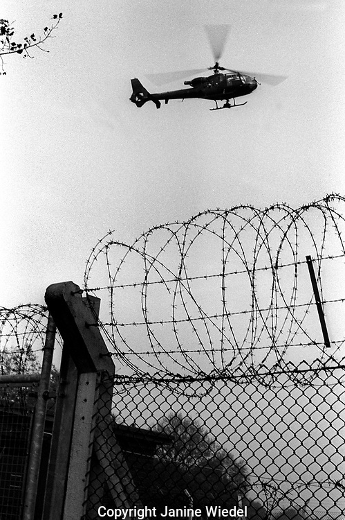 Helicopter surveilling the anti-nuclear Greenham Common Women's Peace Camp in 1983 / 1984. The women only camp surrounded the RAF  base in Berkshire (UK) where American cruise missiles were being stored.