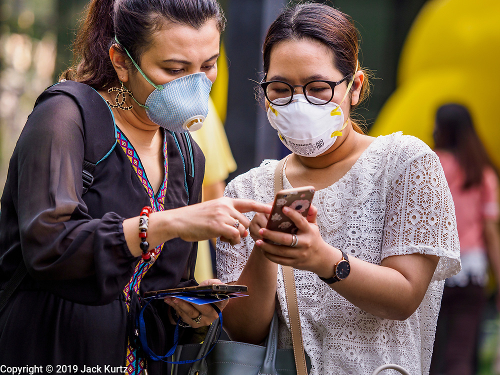 31 JANUARY 2019 - BANGKOK, THAILAND:   Women wearing breathing masks because of Bangkok's high pollution levels look at a smart phone in front of a Bangkok hotel. The Thai government has closed more than 400 schools for the rest of the week because of high levels of pollution in Bangkok. At one point Wednesday, Bangkok had the third highest level of air pollution in the world, only Delhi, India and Lahore, Pakistan were worst. The Thai government has suspended some government construction projects and ordered other projects to take dust abatement measures. Bangkok authorities have also sprayed water into the air in especially polluted intersections to control dust. Bangkok's AQI (Air Quality Index) Thursday morning was 180, which is considered unhealthy for all people.    PHOTO BY JACK KURTZ