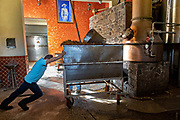 A worker moves a batch of fermented blue agave mash into the still at the Casa Siete Leguas, El Centenario tequila distillery in Atotonilco de Alto, Jalisco, Mexico. After being crushed by a stone mill the agave fibers are mixed with spring water and fermented before being distilled into tequila and then aged in barrels. The Seven Leagues tequila distillery is the oldest family owned distillery producing authentic handcrafted tequila using traditional methods.