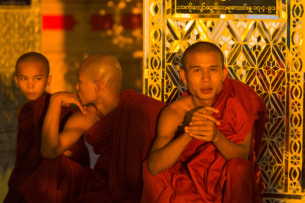 Three monks at the Su Taung Pyi Pagoda atop Mandalay Hill at sunset, Mandalay, Myanmar (Burma)