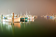 Foggy nights are illuminated by dock lights and street lamps in this sleepy scene of the Port of Galilee at night one summer in southern Rhode Island.
