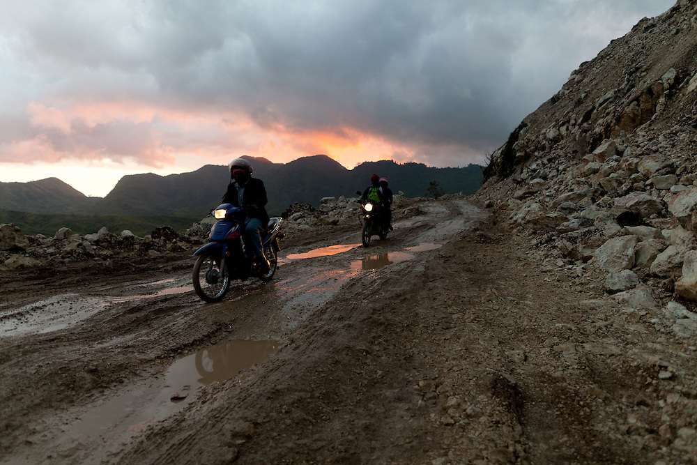 Motorcycles carefully dodge puddles on a muddy section of road at dawn.