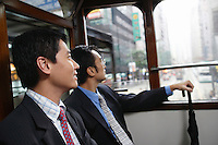 China Hong Kong two business men sitting in double Decker tram side view