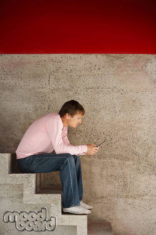 Man Using Cell Phone on Stairs
