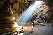 """THAILAND, Kao Luang: 09 November 2015 A enthralled tourist takes a stroll through Tam Kao Luang """"Cave Kao Luang"""" this afternoon as the sun shines through a gap. The cave was consecrated to the memory of King Rama IV by his son King Rama V. Rick Findler / Story Picture Agency"""