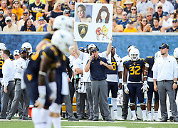Sep 16, 2017; Morgantown, WV, USA; West Virginia Mountaineers head coach Dana Holgorsen calls in a play during the first quarter against the Delaware State Hornets at Milan Puskar Stadium. Mandatory Credit: Ben Queen-USA TODAY Sports