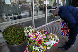 © Licensed to London News Pictures. 16/03/2019. London, UK. A man wearing a London hat and holding a Union Jack carrier bag reads the messages left at High Commission of New Zealand in London. A gunman killed 49 worshippers at the Al Noor Masjid and Linwood Masjid mosques in Christchurch, New Zealand on 15 March. The 28-year-old Australian suspect, Brenton Tarrant, appeared in court on 16 March and was charged with murder. Photo credit: Dinendra Haria/LNP