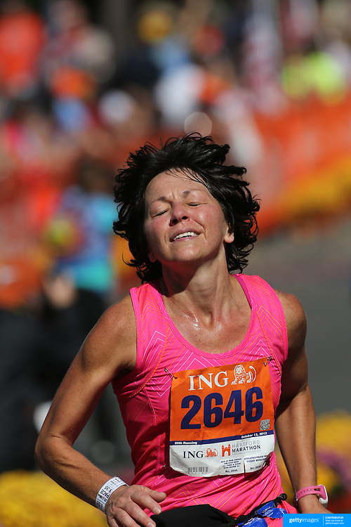 The Finish Line. Expressions of agony and ecstasy on the faces of athletes as Debra Long, Winfield, finishes the ING Hartford Marathon, Bushnell Park, Hartford. Connecticut. USA. Hartford, Connecticut, USA. 12th October 2013. Photo Tim Clayton