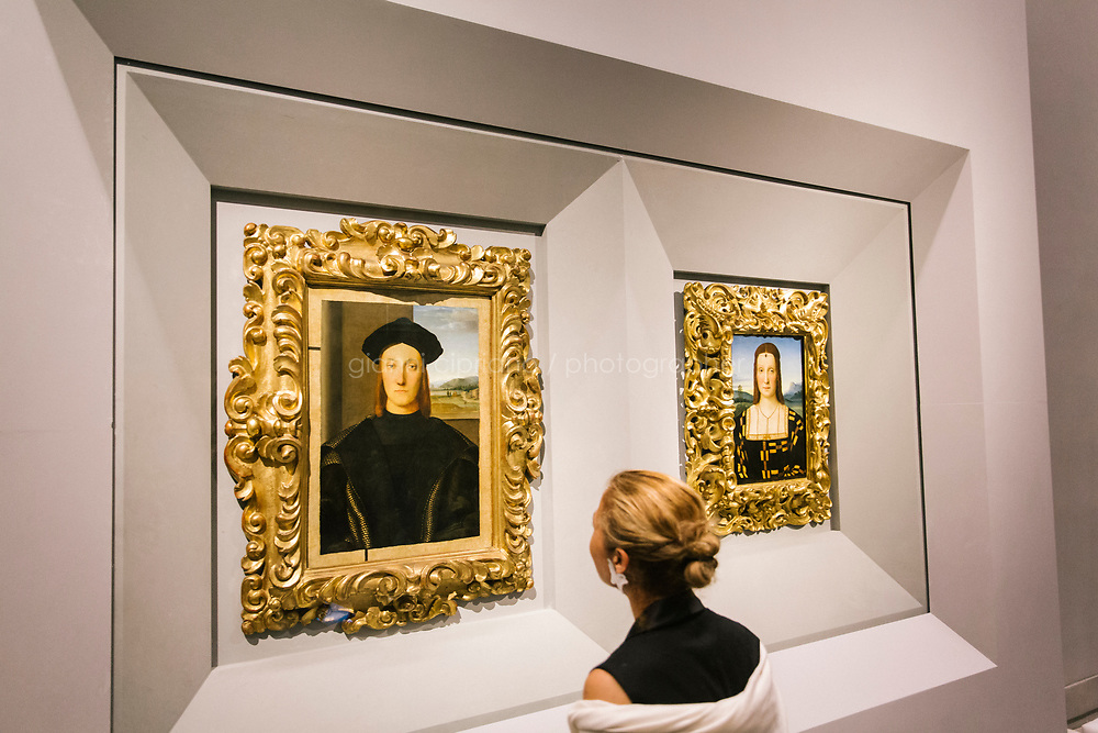 FLORENCE, ITALY - 3 JUNE 2018: A visitor looks at the earlier Raphael portraits of Elisabetta Gonzaga and Guidobaldo<br /> da Montefeltro here in their new location in room 41at the Uffizi, in Florence, Italy, on June 3rd 2018.<br /> <br /> As of Monday June 4th 2018, Room 41 or the &ldquo;Raphael and Michelangelo room&rdquo; of the Uffizi is part of the rearrangement of the museum's collection that has<br /> been defining Uffizi Director Eike Schmidt&rsquo;s grander vision for the Florentine museum.<br /> Next month, the museum&rsquo;s Leonardo three paintings will be installed in a<br /> nearby room. Together, these artists capture &ldquo;a magic moment in the<br /> first decade of the 16th century when Florence was the cultural and<br /> artistic center of the world,&rdquo; Mr. Schmidt said. Room 41 hosts, among other paintings, the dual portraits of Agnolo Doni and his wife Maddalena Strozzi painted by Raphael round 1504-1505, and the &ldquo;Holy Family&rdquo;, that Michelangelo painted for the Doni couple a year later, known as the<br /> Doni Tondo.