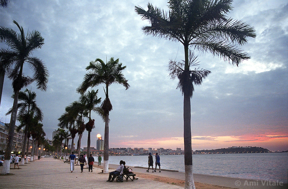 People walk along the main promenade in the capital of Luanda in Angola at dusk in this file photo.  President Jose Eduardo dos Santos, who has led Angola since 1979, said he would not run in presidential elections planned for next year.  Angola's brutal 26 year-civil has displaced around two million people - about a sixth of the population - and 200 die each day according to United Nations estimates. .(Photo by Ami Vitale)