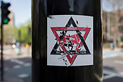 A scratches, defaces sticker of a Jewish anti-facist group at a bus stop at Elephant & Castle, on 23rd April 2018, in London, England.