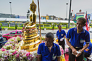 12 APRIL 2014 - BANGKOK, THAILAND: Buddhist layworkers with the Phra Buddha Sihing statue during  the procession's stop in Thonburi. The Phra Buddha Sihing, a revered statue of the Buddha, is carried by truck through the streets of Bangkok so people can make offerings and bathe it in scented oils. Songkran is celebrated in Thailand as the traditional New Year's from 13 to 16 April. The date of the festival was originally set by astrological calculation, but it is now fixed. The traditional Thai New Year has been a national holiday since 1940, when Thailand moved the first day of the year to January 1. The first day of the holiday period is generally the most devout and many people go to temples to make merit and offer prayers for the new year.    PHOTO BY JACK KURTZ