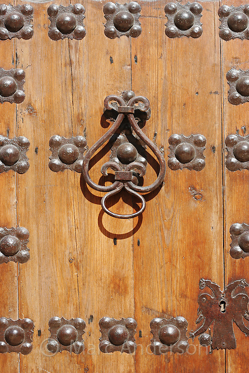 Details of studs & knocker on an old wooden door in Spain.
