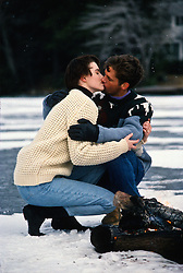 Couple outdoors in the winter kissing by a fire on a frozen lake