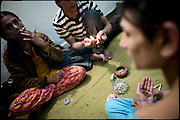 "Sery (on the left), 29 years old, C. (in the middle), 28 years old, and Kastouri, 16 years old, all transvestites, prepare a couple of cigaretttes with hashish, at their  common apartment. Most of the transvestites people live an extremely marginalized life, far from their own families, because often sent away from house. Evening in Lahore, Pakistan on Monday, December 01 2008.....""Not men nor women"". Just Hijira, Kusra. Painted lips, Kajal surrounding their eyes and colourful veils..Pakistan is today considered a strongly, foundamentalist as well, islamic country. But under its reputation, above all over the talebans' continuos advancing, stirs a completely extraneous world, a multiethnic mixed society. Transvestites make part of it, despite this would not be admitted by a strict law. Third gender, the Hijira are born as men (often ermaphrodites) or with an ambiguous genital situation, and they have their testicles and penis removed through a - often brutal - surgical operation. The peculiarity is that this operation does not contemplate the reconstruction of a female organ. This is the reason why they are not considered as men nor women, just Hijira. They are often discriminated, persecuted  and taxed with being men prostitutes in the muslim areas. The members of this chast perform dances during celebrations, especially during weddings, since it is anciently believed that an EUNUCO's dance and kiss in the wedding day brings good luck to the couple's fertility...To protect the identities of the recorded subjects names and specific .places are fictionals."