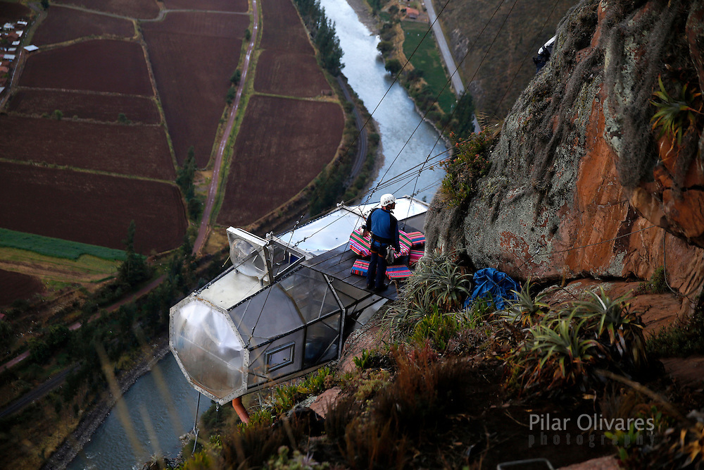 "A guide waits for guests above the sleeping pod at the Skylodge Adventure Suites in the Sacred Valley in Cuzco, Peru, August 14, 2015. Tourists taking on an arduous climb up the steep cliff face of Peru's Sacred Valley are being rewarded for their efforts by being able to spend the night in transparent mountaintop sleeping pods at the ""Skylodge Adventure Suites"". To reach the pods, visitors need to climb 400 metres of via ferrata (a steel cable and rungs) up the valley side or hike an intrepid trail through zip lines. REUTERS/Pilar Olivares"