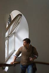 man walking in a stairwell by a window