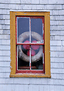 Window on seaside house in coastal village on the island of Nova Scotia in Canada Scenic view of Digby, Nova Scotia Harbor on the Bay of Fundy with Scallop, Lobster,Halibut and Cod fishing boats common in the upperAtlantic coast.