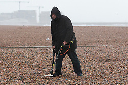 © Licensed to London News Pictures. 26/01/2016. Brighton, UK. A man with his metal detector braves the  wind and rain on Brighton seafront as the remains of Storm Jonas reach the UK from the USA. Photo credit: Hugo Michiels/LNP