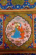 Detail from Persian manuscript depicting lovers embracing in garden, surrounded by flowering plants. Clouds in sky.