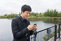 Happy mid adult businessman text messaging through mobile phone at bridge railing