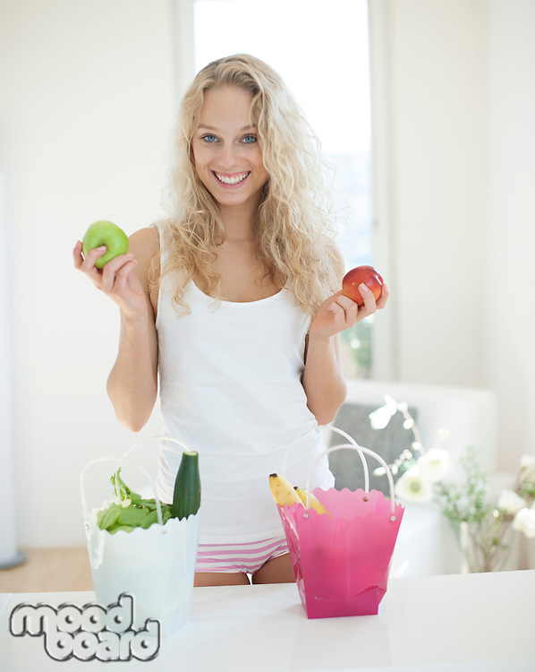 Portrait of young woman holding apples at kitchen counter
