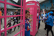 A line of information kiosks, pretend phone boxes provided by Newjam Council, the borough hosting during the London 2012 Olympics, the 30th Olympiad. As a team member makes a call outsidethe iconic shape of the red telephone box known as the quintessential British design, crowds of spectators and travellers pass-by near the main Olympic Park complex. A mother pushes her child's buggy and Newham employees hand out local maps and info to Olympic visitors.