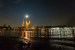 © Licensed to London News Pictures. 08/09/2014. London, UK. A tall ship on the River Thames is illuminated by a full harvest moon as it passes by the Old Royal Naval College in Greenwich on the evening of 8th September 2014. The Royal Greenwich Tall Ships Festival takes place in London from 5-9 September 2014. Photo credit : Vickie Flores/LNP