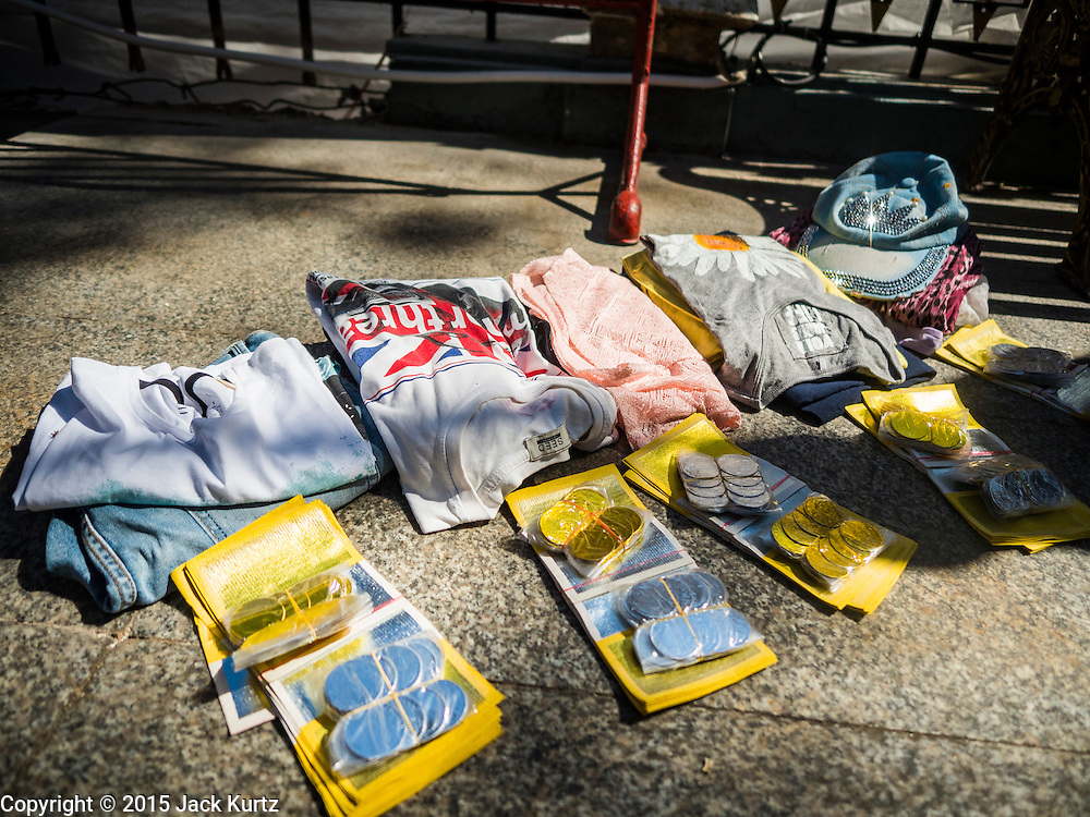 19 AUGUST 2015 - BANGKOK, THAILAND:  A memorial consisting of clothes and coins left for Malaysians who died in the terror bombing at Erawan Shrine. Erawan Shrine in Bangkok reopened Wednesday morning after more than 20 people were killed and more than 100 injured in a bombing at the shrine Monday, August 17, 2015. The shrine is a popular tourist attraction in the center of Bangkok's high end shopping district and is an important religious site for Thais. No one has claimed responsibility for the bombing.      PHOTO BY JACK KURTZ