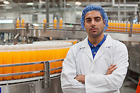 Portrait of confident factory worker standing with arms crossed