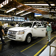 Workers check vehicles coming off the inspection line as President Bush tours the Ford Motor Company -- Kansas City Assembly Plant Tuesday, March 20, 2007, in Kansas City, MO.  Tour guides are Mayor Jim Stoufer; Alan Mulally, President and CEO of Ford Motor Company; Ken Ward, Plant Manager. <br /> <br /> Photo by Khue Bui
