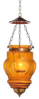 orange glass hanging outdoor lantern with lit candle