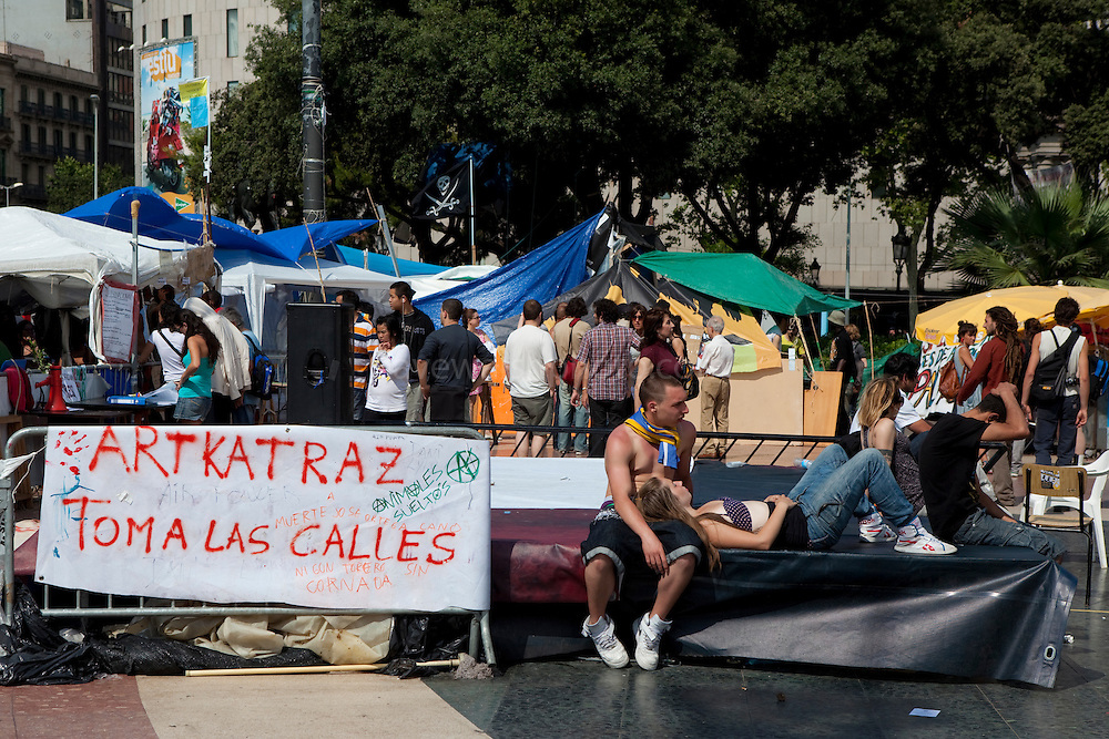 "People enjoying afternoon sun at the antigovernment protest camp at Placa de Catalunya, Barcelona, Spain. Banner reads: Artkatraz takes to the streets"". The square has been relatively quiet since police attacked and beat protestors on May 27 2011."