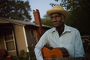 "BESSEMER, AL – OCTOBER 8, 2011: Blues legend Henry ""Gip"" Gipson, 90, strums an acoustic guitar in front of his home before his weekly performance in his backyard juke joint.<br /> <br /> After an altercation with the KKK in the 60's rendered his left hand badly broken, Gipson's method of guitar playing had to change. ""I had to crowd the strings,"" Gipson said, describing the method that he adopted. Today, Gipson operates Gip's Place, one of few true remaining juke joints in the country. ""Music don't care no color,"" Gipson said. ""And that's why I love blues, because blues deals with a story to tell you."""