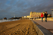 Tourists brave stormy weather near the Hôtel du Palais on the Grand Plage, Biarritz, Basque Country, France