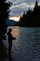 Scott Clem, a student from Auburn University, fishes for salmon at sunset on the Chilkoot River outlet from Chilkoot Lake near Haines, Alaska. The river offers some of the best salmon fishing in Southeast Alaska, with four salmon runs, starting in mid-June and ending in mid-October. The area is part of the Chilkoot Lake State Recreational Site located at the head of the Lutak Inlet in the Lynn Canal. It is managed by Alaska State Parks. In the upper reaches of the Chilkoot River Valley (not pictured) Alaska Power and Telephone Company (AP&T) proposes to dam the outlet of Connelly Lake, a high alpine lake above the Chilkoot River, for a hydroelectric project. Water from Connelly Lake would be delivered down the mountain to a powerhouse near the Chilkoot River into which the lake water would be discharged. Environmental concerns include the impact construction and project operation would have on fish spawning and rearing habitat (water turbidity issues), and bald eagles. Some of the main features of the proposed Connelly Lake project would be located in the Alaska Chilkat Bald Eagle Preserve and the Haines State Forest. The Connelly Lake Hydro Aquatic Studies Report for 2012 prepared by the Shipley Group for AP&T states that according to the Alaska Department of Fish and Game, 41 percent of the sockeye salmon in the upper Lynn Canal come from the Chilkoot River with 25 percent of those salmon spawning in the Chilkoot River drainage above Chilkoot Lake. The value of the fishery is estimated at more than $1,000,000 annually. AP&T wants to build the project to replace the undersea cable that supplies Haines with electricity from Skagway.