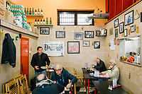 NAPLES, ITALY - APRIL 10th 2018: Customers have lunch at the Trattoria Malinconico, a popular restaurant in the Vomero district in Naples, Italy, on April 10th 2018.<br /> <br /> Trattoria Malinconico was opened in 1953 by current owner Marianna Sorrentino's parents-in-law. At first it was only a bulk wine cellar, but then he began making a few cooked dishes – small plates that were popular with locals, which eventually morphed into larger meals. Still today the trattoria is frequented the neighborhood's older residents, many of whom have been loyal regulars for years, as well as younger locals and workers, who often stop by for a glass of wine. The menu varies from day to day, and is typically based on traditional Neapolitan recipes. Though some dishes, like meatballs, sausages, and friarielli (rapini, a type of broccoli typical to Naples), are always available.<br />  <br /> <br /> Genovese sauce is a rich, onion-based pasta sauce from the region of Campania, Italy. Likely introduced to Naples from the northern Italian city of Genoa during the Renaissance, it has since become famous in Campania and forgotten elsewhere.<br /> Genovese sauce is prepared by sautéing either beef, veal or pork in a large number of onions, for at least two but as many as ten hours. Large, cylindrical pasta like rigatoni, ziti or candele are favored because they can hold the rich sauce.