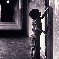 A child speaks to an unseen person behind a door in Chicago's Cabrini Green housing development in 1981.
