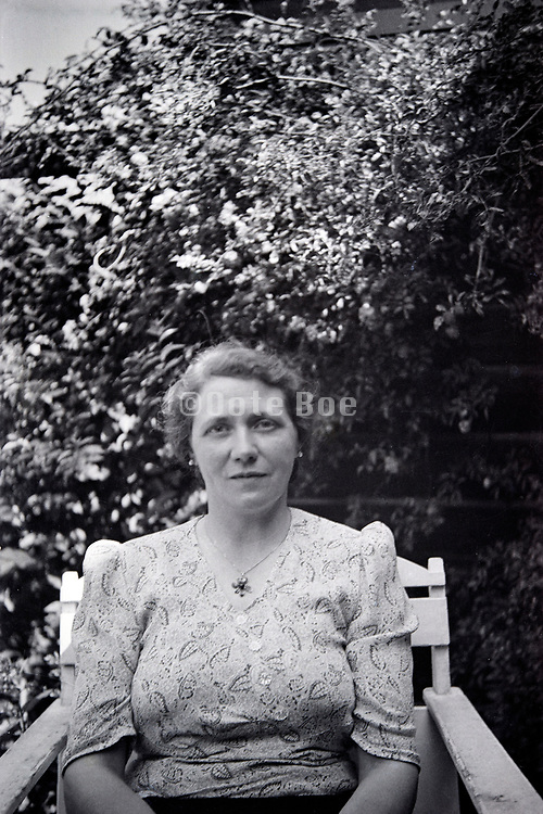 woman posing in chair with garden hedge background 1950s Netherlands