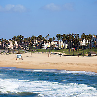 Photo of Huntington Beach shoreline, people at the beach, and houses along Pacific Coast Highway. Huntington Beach is also known as Surf City USA and is a seaside beach city along the Pacific Ocean in Orange County Southern California.
