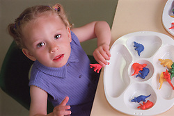 Nursery school girl sitting at desk in classroom playing with plastic toys,