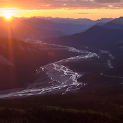 The sun sets over the MacDonald Creek Valley and the meandering Alaska Highway in Stone Mountain Provincial Park, northern British Columbia