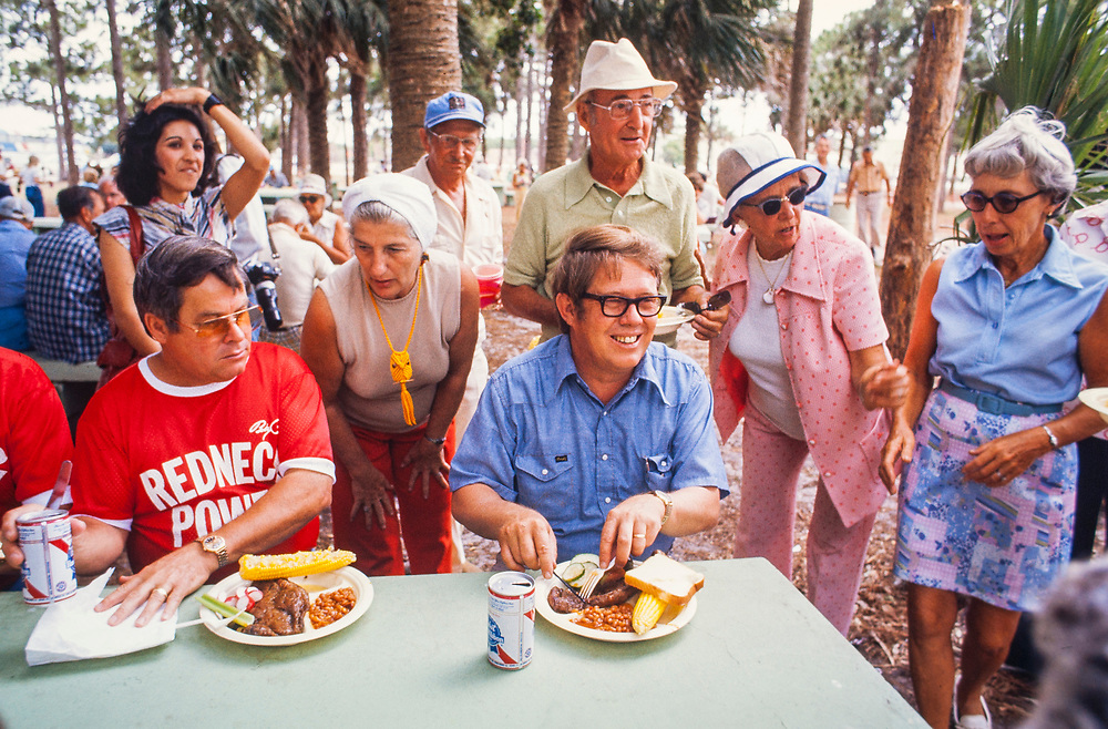 "A smiling Billy Carter at a picnic lunch in West Florida. William Alton - Billy - Carter (March 29, 1937 – September 25, 1988) was an American farmer, businessman, brewer, and politician, and the younger brother of U.S. President Jimmy Carter. Carter promoted Billy Beer and was a candidate for mayor of Plains, Georgia. Carter was born in Plains, Georgia, to James Earl Carter Sr. and Lillian Gordy Carter. He was named after his paternal grandfather and great-grandfather, William Carter Sr. and William Archibald Carter Jr. respectively. He attended Emory University in Atlanta but did not complete a degree. He served four years in the United States Marine Corps, then returned to Plains to work with his brother in the family business of growing peanuts. In 1955, at the age of 18, he married Sybil Spires (b. 1939), also of Plains. They were the parents of six children: Kim, Jana, William ""Buddy"" Carter IV, Marle, Mandy, and Earl, who was 12 years old when his father died."